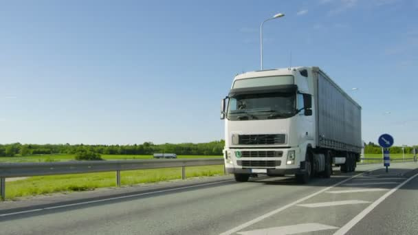 Speeding White Semi Truck with Cargo Trailer Drives on the Highway. Weather is Sunny, Road is Empty.