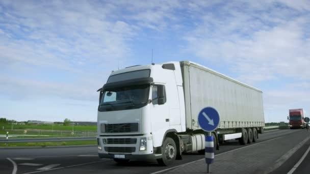 Rasender weißer Sattelschlepper mit Ladeanhänger fährt auf die Autobahn. LKW steht an erster Stelle in der Kolonne der schweren Fahrzeuge, die Sonne scheint.