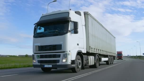 Speeding White Semi Truck with Cargo Trailer Drives on the Highway. Truck is First in the Column of Heavy Vehicles, Sun is Shining.