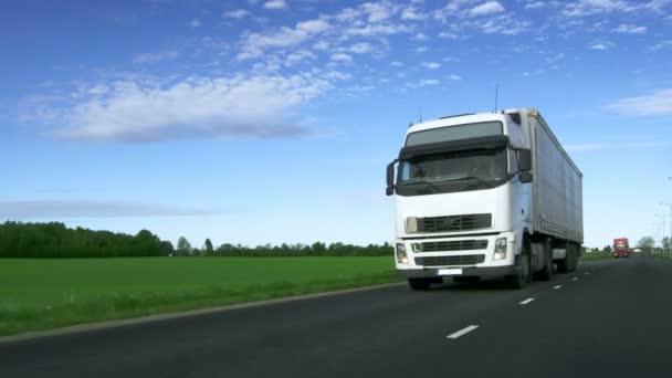Rasender weißer Sattelzug mit Ladeanhänger fährt auf Autobahn mit Feldern am Straßenrand.