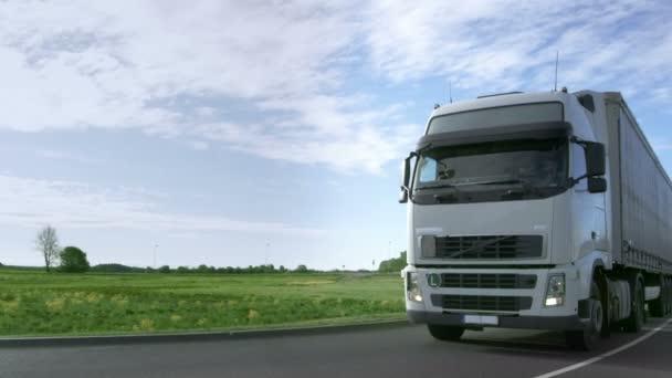 Čelní pohled rychlosti bílé Semi Truck s nákladní přívěs jednotkami na dálnici s poli a průmyslové sklady v pozadí.