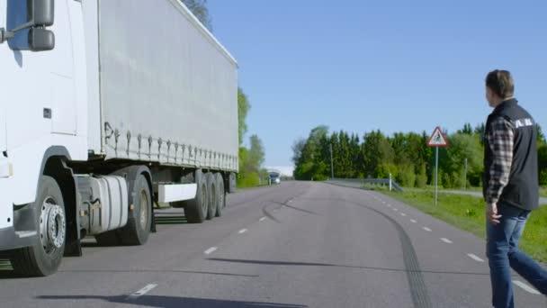 Autista di camion attraversa la strada e ottiene nel suo camion Semi bianca parcheggiata con rimorchio carico associata. Sole splende e lautostrada è vuoto.