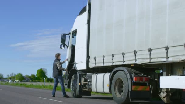 Truck Driver Crosses the Road in the Rural Area and Gets into His White Semi Truck with Cargo Trailer Attached. Sun Shines and Highway is Empty.