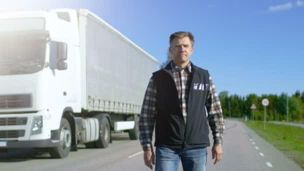 Profesionální řidič dostane z zaparkovaná bílá Semi Truck s nákladní přívěs připojený. Řidič stojí uprostřed silnice a hrdě kříže zbraní