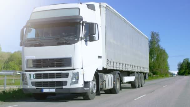 Lastwagenfahrer steigt aus seinem geparkten weißen Kastenwagen. Tag ist sonnig, Fahrer ist professionell.
