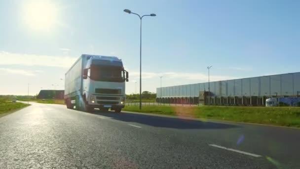Velké bílé Semi Truck s nákladní přívěs se pohybuje na silnici prázdná oblast průmyslového skladu s slunce zářící na pozadí.