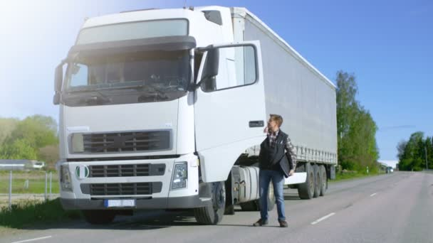 Truck Driver with Freight Documents Folder Gets out of His Parked White Cab-Over Truck and Crosses the Road.
