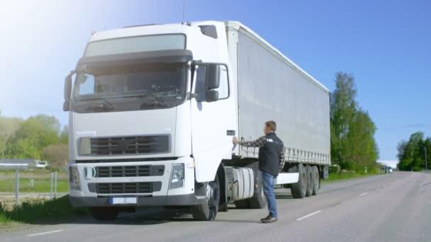 Řidič dostane ven zaparkovaná bílá Semi Truck s nákladní přívěs připojený. Profesionální řidič protíná silnici na tento krásný slunečný den