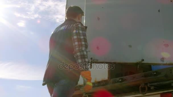 Řidič kamionu zavře dveře jeho přívěs nákladní vůz. Profesionální řidič nosí rukavice Heavy Duty.