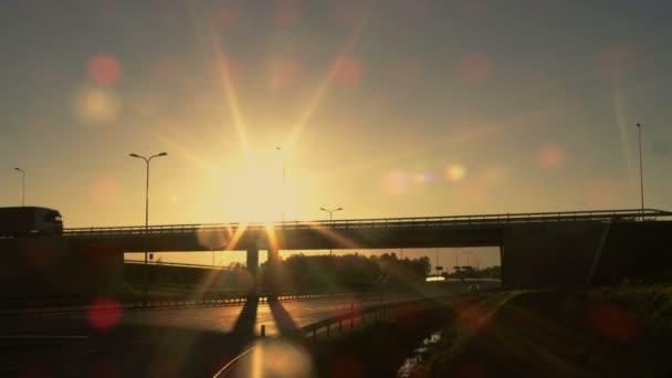 Boční pohled bílé Semi Truck s nákladní přívěs jízda přes most. Krásné scenérie s vozidlem jedoucím na nadjezdu. Je stále tma a slunce zapadá.