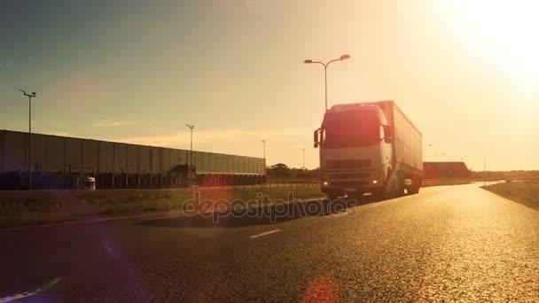 Bílá Semi Truck s nákladní přívěs připojené jednotky na prázdnou silnici. Průmyslové sklady stranami dálnice. Západ slunce.