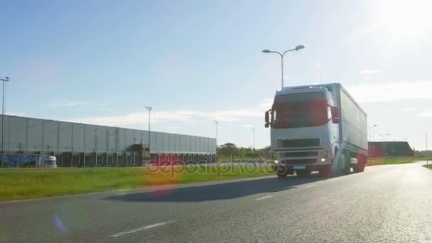 Bílá Semi Truck s nákladní přívěs připojené jednotky na prázdnou silnici. Průmyslové sklady stranami dálnice a slunce svítí.