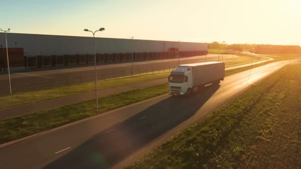 Aerial View of White Semi Truck with  Cargo Trailer Moving on the Highway. In the Background Warehouses and Rural Area, Sun is Setting. Aerial Side View of White Semi Truck with  Cargo Trailer Moving on the Highway. In the Background Warehouses and R