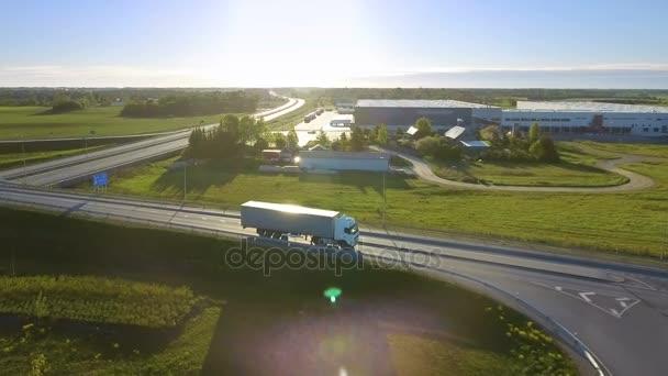 Luftaufnahme eines weißen Sattelzugs mit Ladeanhänger, der an der Autobahnüberführung / Brücke vorbeifährt. Achtzehn Räder sind neu, im Hintergrund sind Laderäume zu sehen.