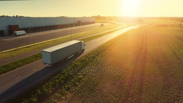 Aerial Follow Shot of White Semi Truck with Cargo Trailer Attached Moving Through Industrial Warehouse, Rural Area. Slunce svítí a obloha je modrá.