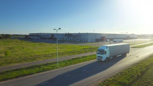 Letecký snímek následovat bílého náklaďáku s návěs připojen, pohybující se po průmyslové skladu, venkovské oblasti. Západ slunce