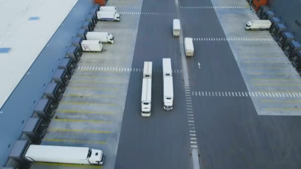 Letecký záběr Truck s připojené Semi přívěs opuštění průmyslového skladu / skladovací budova / načtení oblasti, kde mnoho nákladních vozidel jsou zatížení / uvolnění zboží