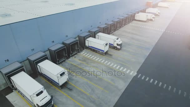 Moving Aerial Side Shot of Industrial Warehouse Loading Dock where Many Truck with Semi Trailers Load/ Unload Merchandise.