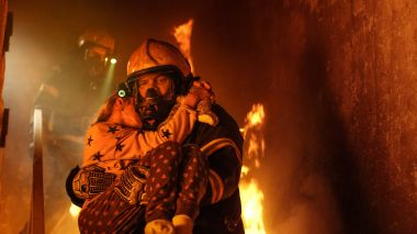 Brave Fireman Descends Stairs of a Burning Building and Holds Sa