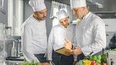 V moderní kuchyni týmu kuchařů použití tabletového počítače pro pří