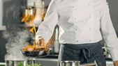 Close-up Shot Fireing ropy na sítě Pan. Flambe, styl vaření. COO