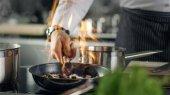 Profesionální kuchař vaří Flambe stylu. Připravuje jídlo v pánvi