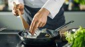 Slavný šéfkuchař restaurace otočí ryb na horkou pánev. Detail Sh