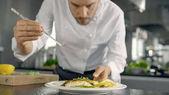 Slavný šéfkuchař zdobí jeho speciální rybí pokrm s nějakou zelení. On