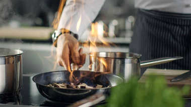 Professional Chef Cooks Flambe Style. He Prepares Dish in a Pan