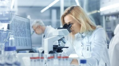 Female Research Scientist Looks at Biological Samples Under Micr