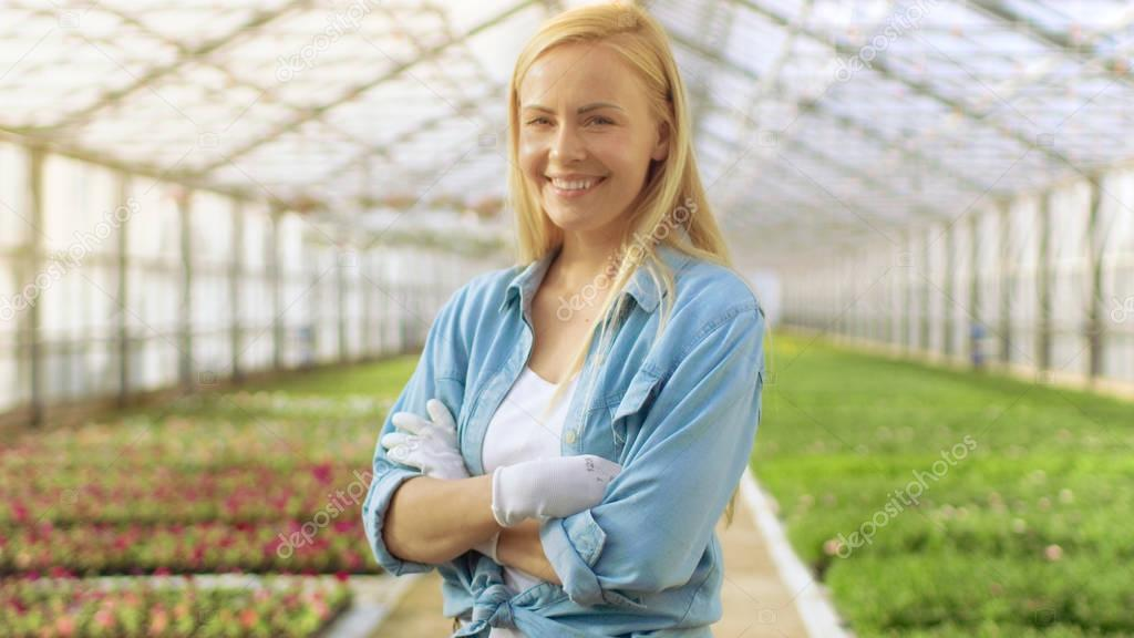 On a Sunny Day Beautiful Blonde Gardener Stands Smiling in a Gre