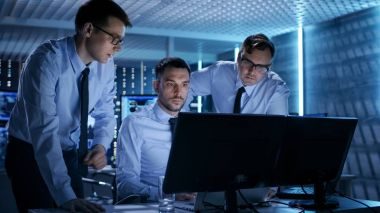Three Operations Engineers Solving Problem in a Monitoring Room.