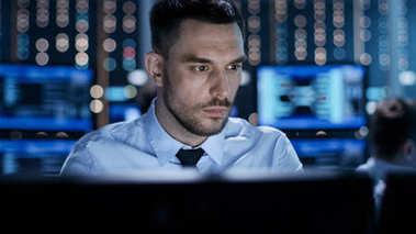 Close-up of a Professional Technical Controller Sitting at His D
