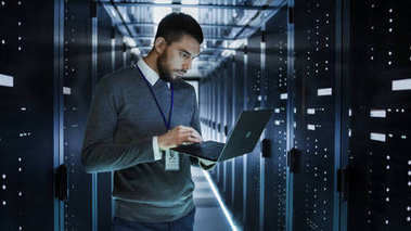 IT Technician Works on a Laptop in Big Data Center full of Rack