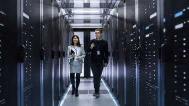 Caucasian Male and Asian Female IT Technicians Walking through C