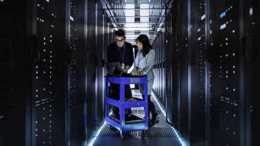 Caucasian Male and Asian Female IT Technicians Working at Large