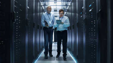 In Data Center Two IT Engineers Walking Through Rows of Server R