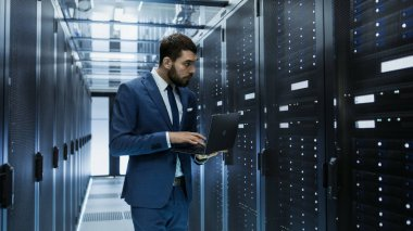 IT Engineer in Data Center Stands Before Server Rack Cabinet Wor