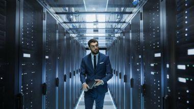 Data Center Technician Walking Through Server Rack Corridor Visu