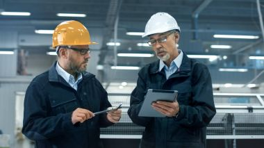 Two engineers in hardhats discuss information on a tablet computer while standing in a factory. stock vector