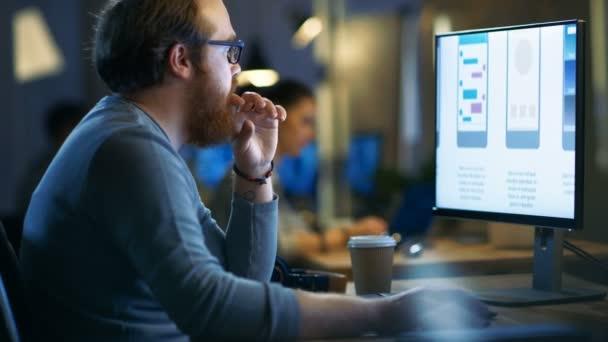 Männliche Mobile Application Developer arbeitet mit Grafiken in seinem persönlichen Computer mit zwei Bildschirmen. Büro-Loft teilt er mit anderen kreativen Menschen.
