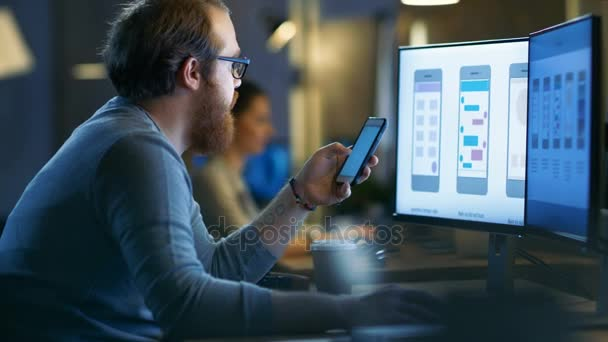 Männliche Mobile Anwendungs-Designer prüft neue Features auf seiner Smarthone, er arbeitet auf einem PC mit zwei Displays in einer kreativen Büroräume.