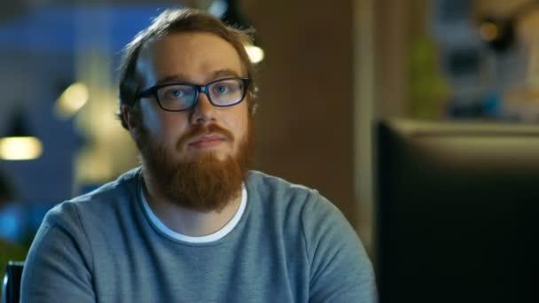 Mladý vousatý kreativní člověk s brýlemi si myslí, že na problém při práci na svém osobním počítači. Vypadá s úsměvem do kamery