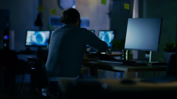 an einem frühen Morgen sitzt der Entwickler mobiler Anwendungen an seinem Schreibtisch und beginnt zu arbeiten, er ist allein im Büro.