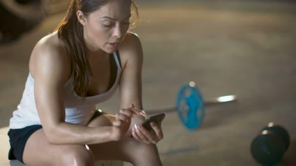 Krásné sportovní bruneta používá Smartphone při odpočinku na lavičce po její intenzivní Cross Fitness kulturistika tělocvik.
