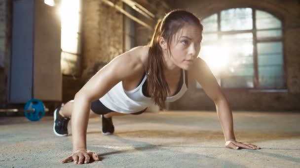 athletisch schöne Frau macht Liegestütze als Teil ihrer Crossfitness, Bodybuilding-Gymnastik-Routine.