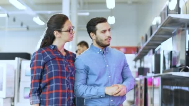 Mladý pár nakupovat pro nový 4k televizorů v obchodě s elektronikou. Jsou to rozhodnutí o nejlepší Model pro jejich šťastný rodinný dům