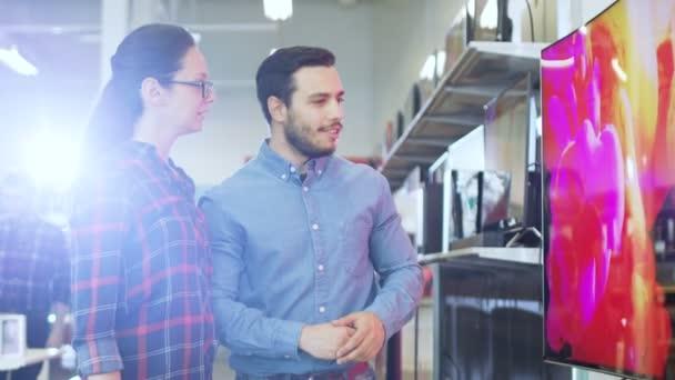 Fiatal pár vásárolni egy új 4k Uhd televízió elektronikai áruház. Ők döntenek a legjobb modell, a boldog családi ház