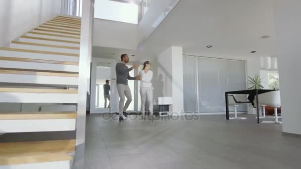 Beautiful Young Couple Enters Their Newly Purchased House, Theyre Very Happy and Their Home is Bright and Modern.