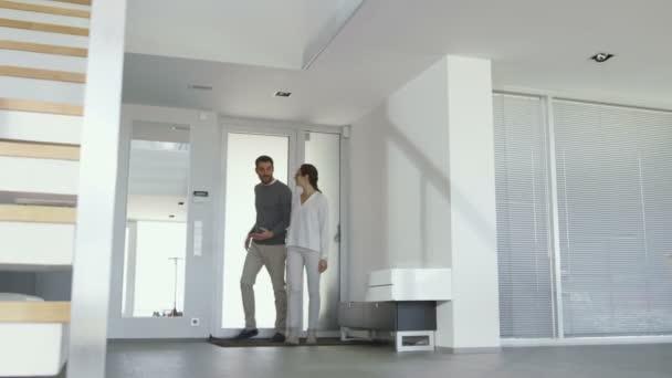 Krásný mladý pár vstoupí do jejich nové světlé a moderní dům. Jsou šťastní, rodinu a muž objímá svou ženu.